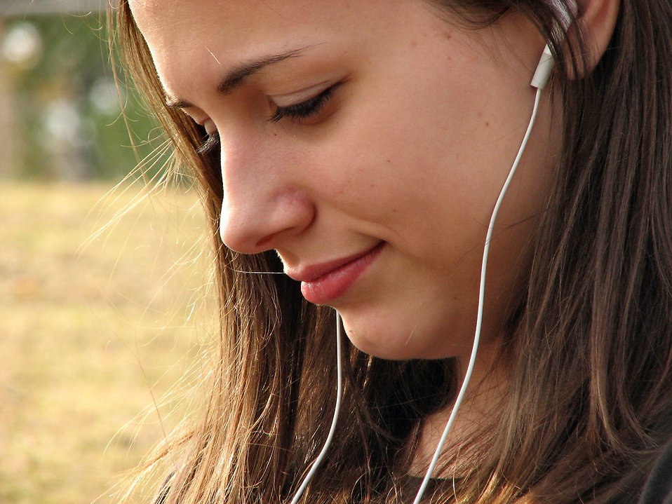 A teenage girl listening to a music player. : Free Stock Photo