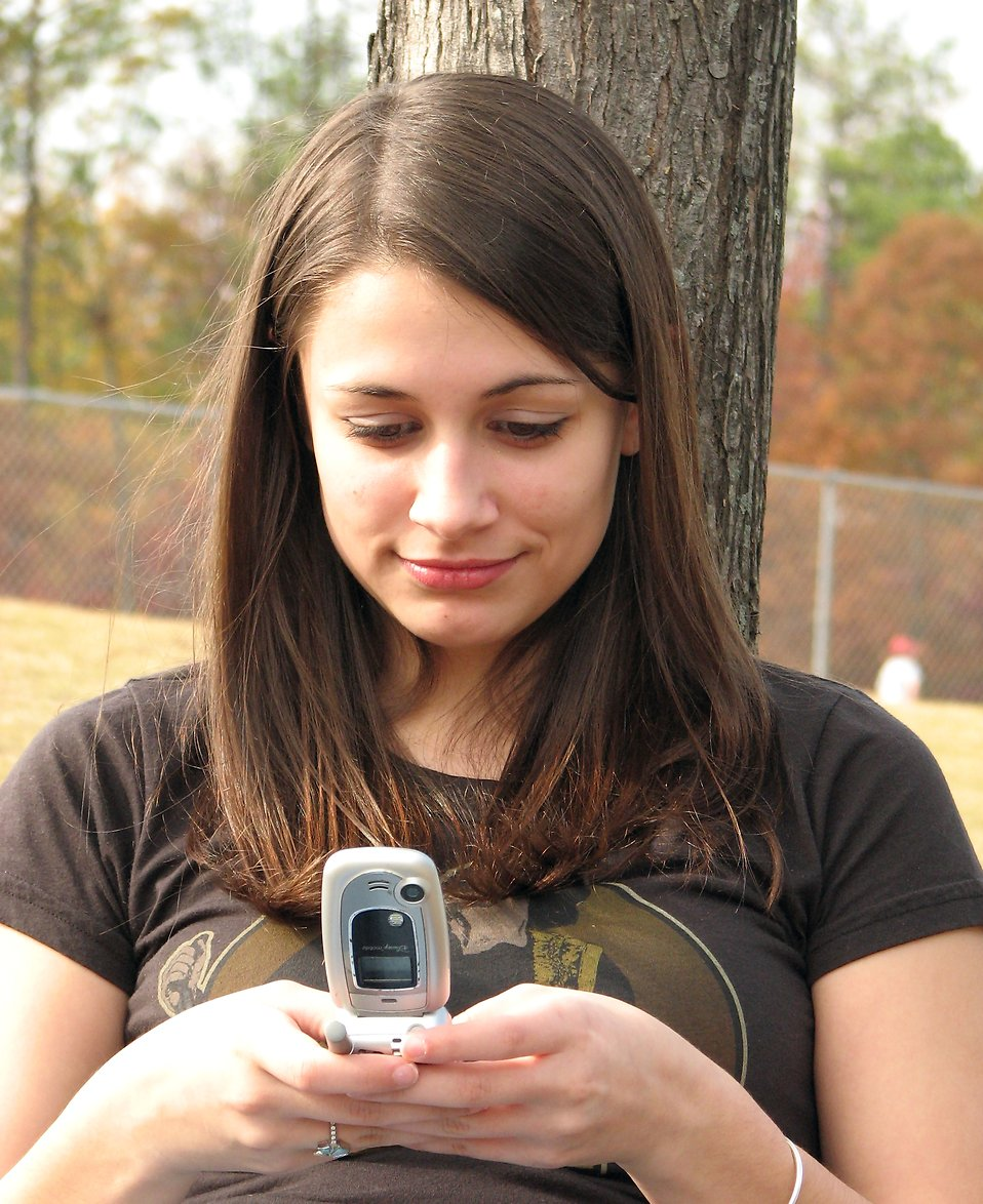 A teenage girl text messaging on a phone : Free Stock Photo ?