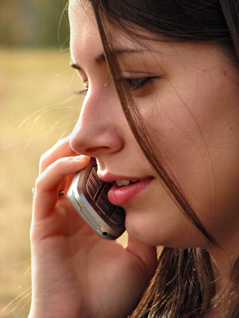 Closeup of a girl talking on a cell phone : Free Stock Photo