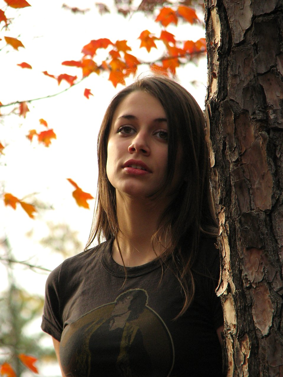 A teenage girl leaning on a tree : Free Stock Photo