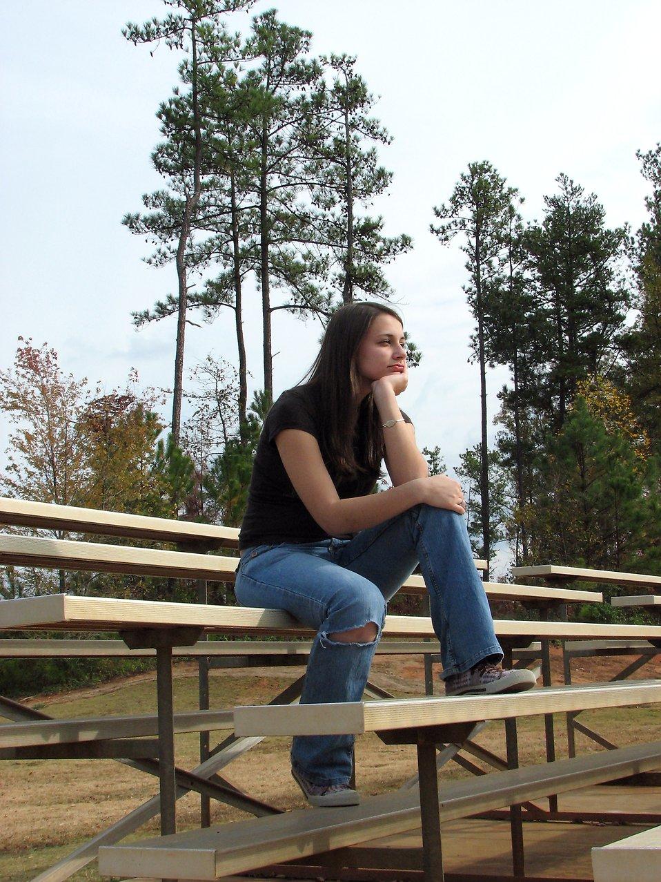 A teenage girl sitting on bleachers : Free Stock Photo