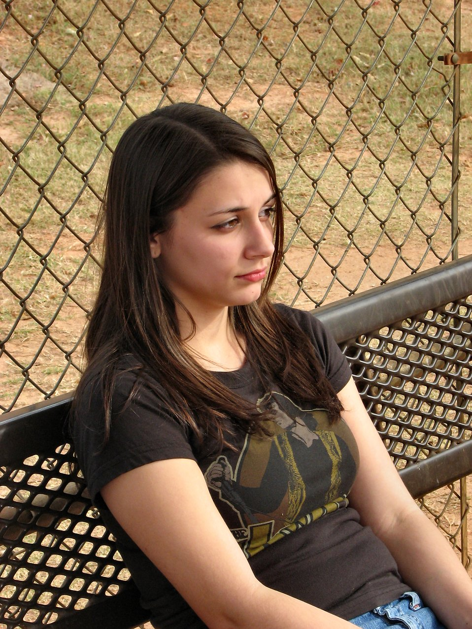 A teenage girl sitting on a bench outside : Free Stock Photo