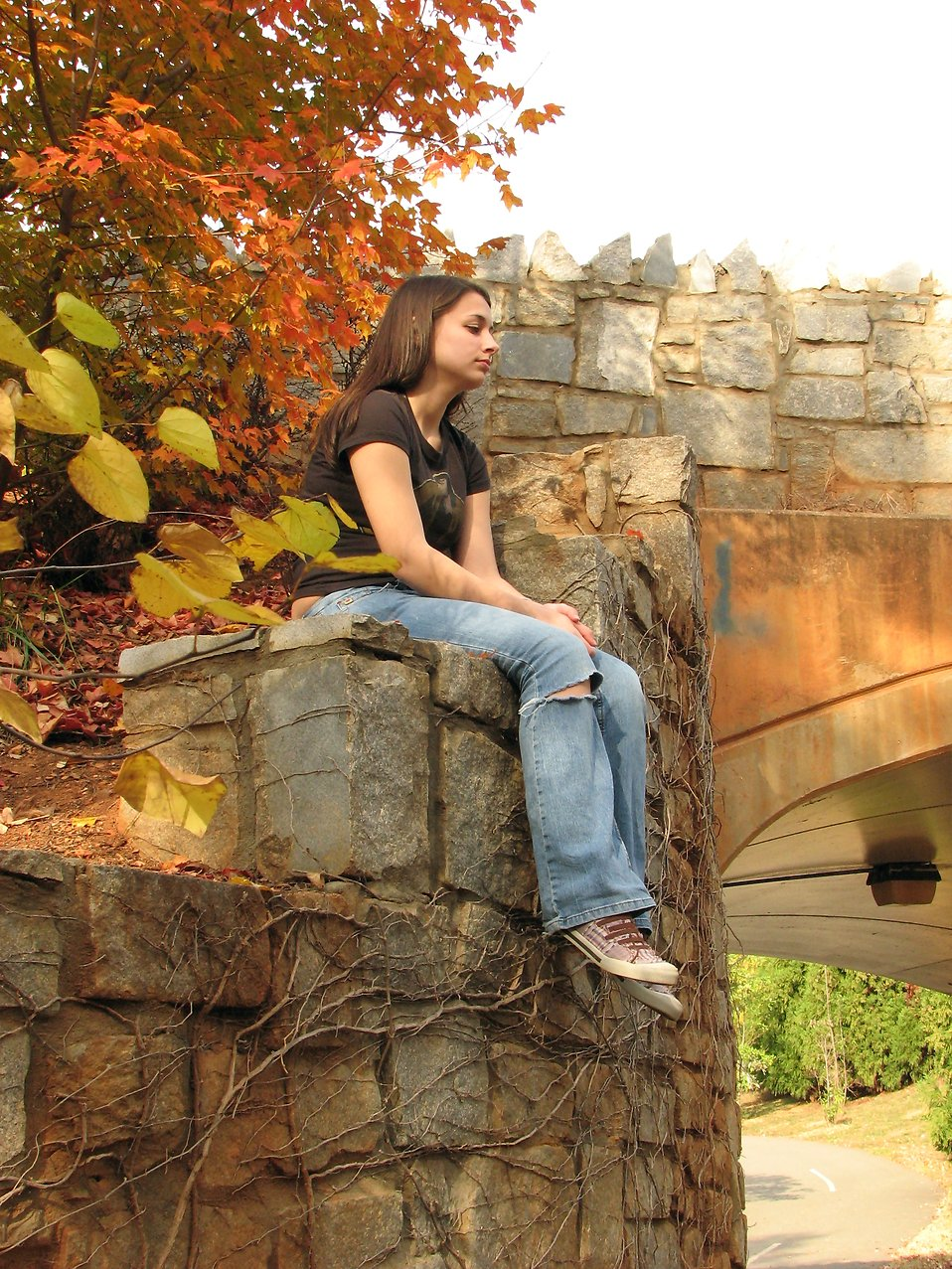 Teen girl sitting by a bridge : Free Stock Photo
