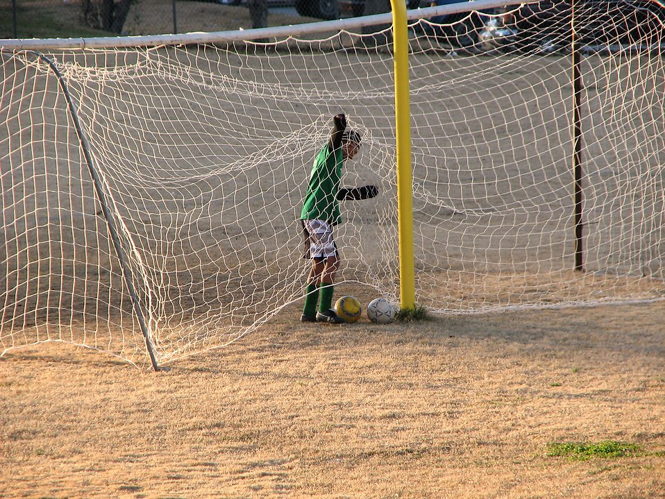 Boy playing in a soccer goal net : Free Stock Photo