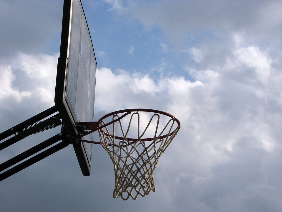 An outdoor basketball hoop with a cloudy sky background.
