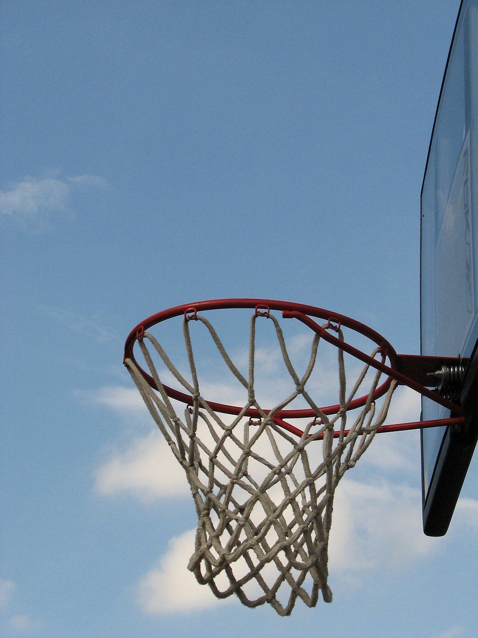 An outdoor basketball hoop with a blue sky background.