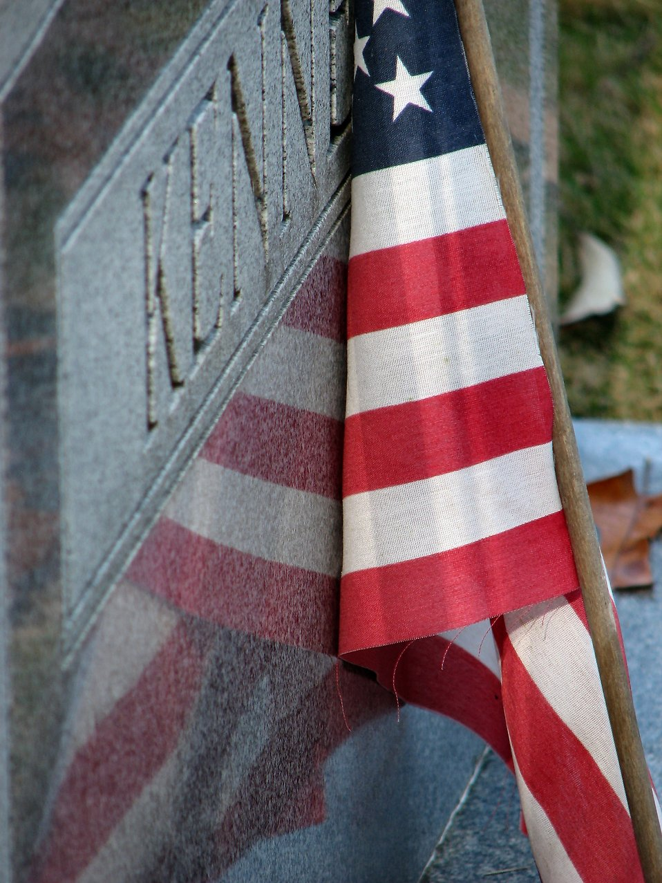 US flag leaning on a tombstone : Free Stock Photo