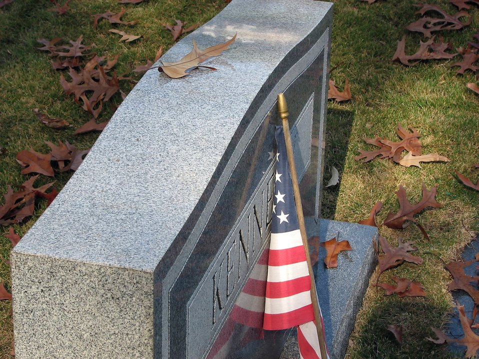 US flag leaning against a tombstone : Free Stock Photo