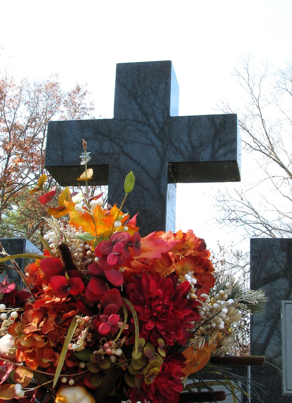 Flowers by a cross in a cemetary : Free Stock Photo