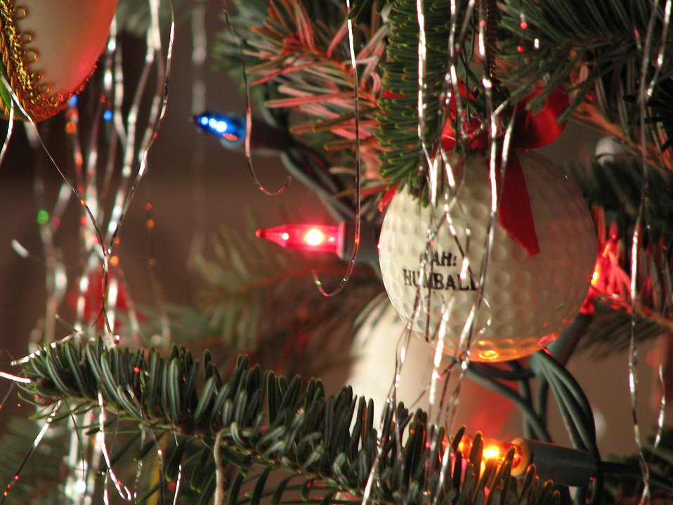 Closeup of a golf ball ornament in a Christmas tree.