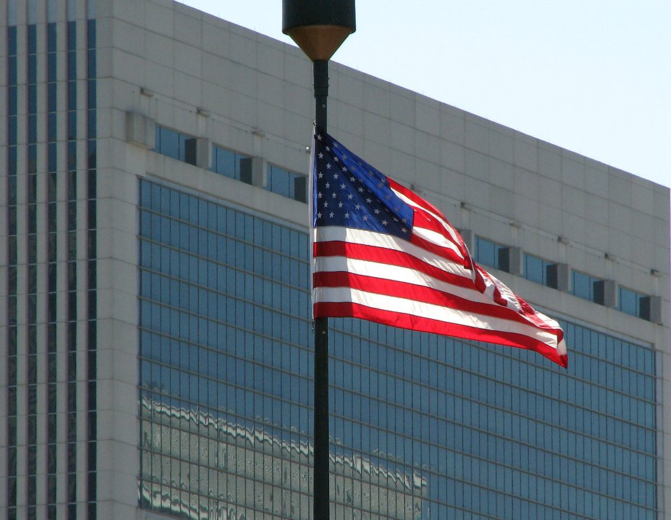 US flag in front of a modern glass building : Free Stock Photo