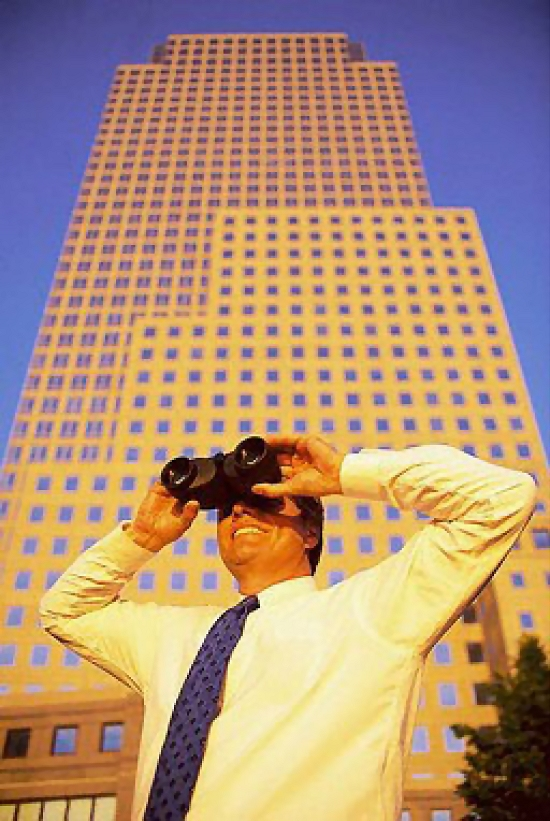A business man looking with binoculars in front of a building.