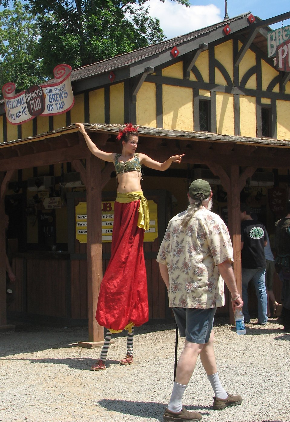 Female acrobat on stilts giving directions : Free Stock Photo