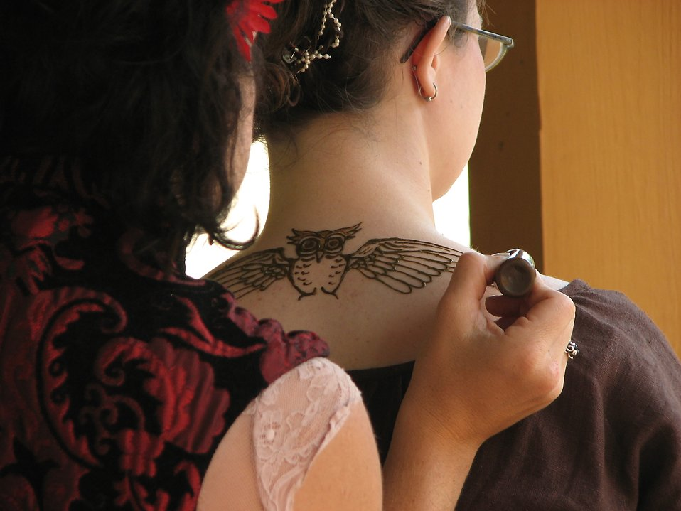 Free Stock Photo: A girl getting a temporary tattoo of an owl on her neck at