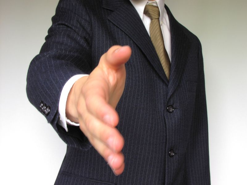 Business man in a blue suit extending his hand for a handshake.
