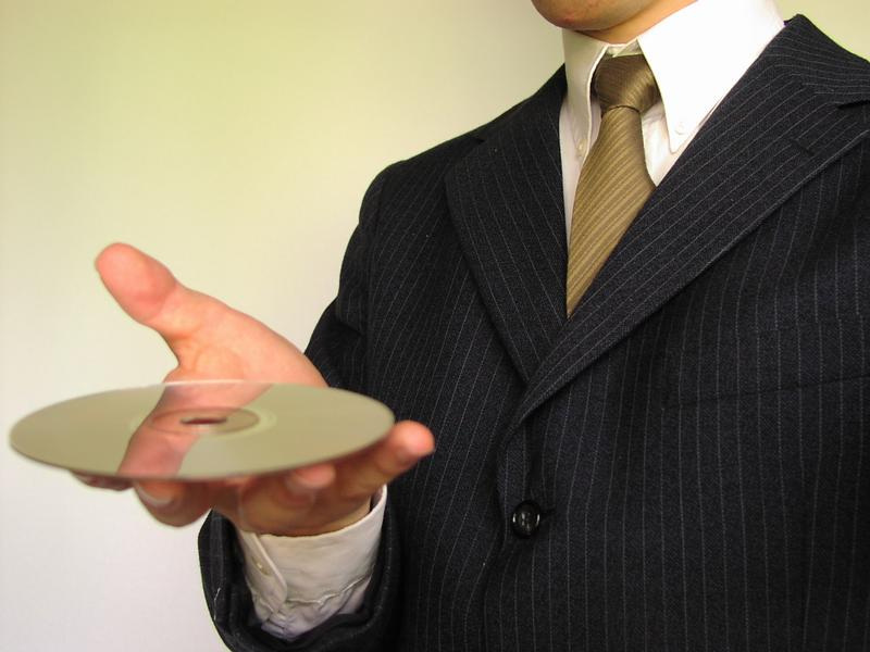 Business man holding a comopact disc : Free Stock Photo