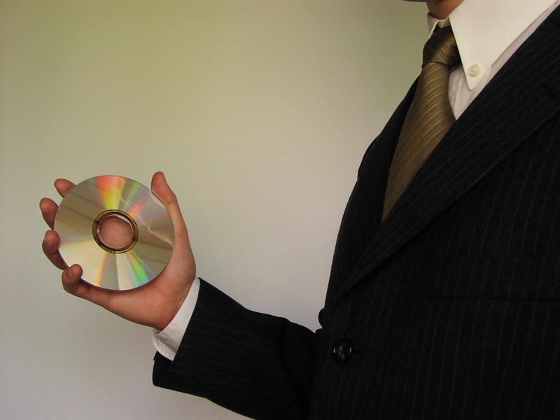 Business man in suit holding a compact disc : Free Stock Photo