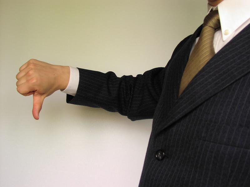 Business man in a suit and tie giving the thumbs down symbol. : Free Stock Photos