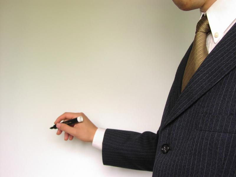 Business man holding a marker beginning to write.