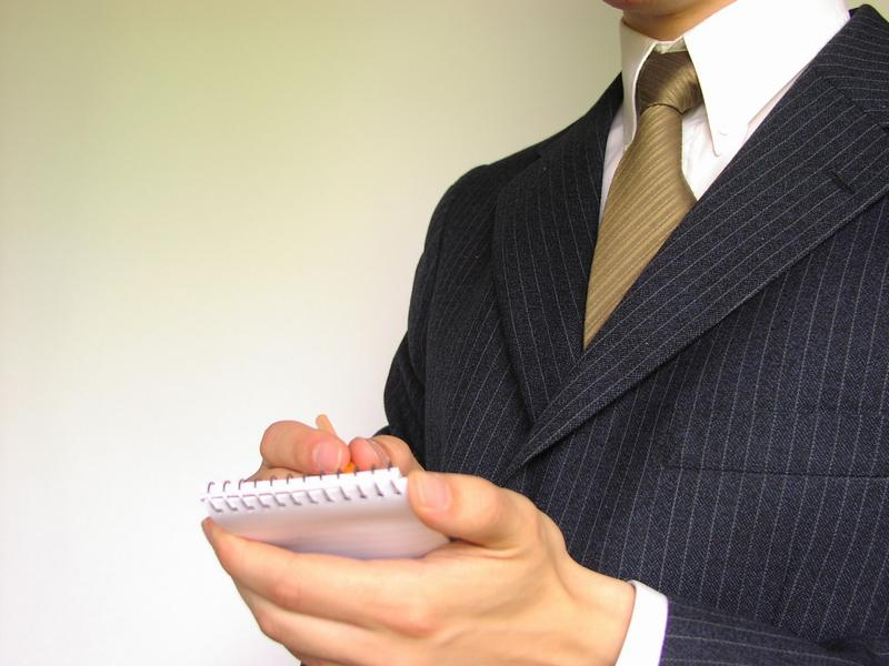 Business man in a suit writing on a memo pad : Free Stock Photo