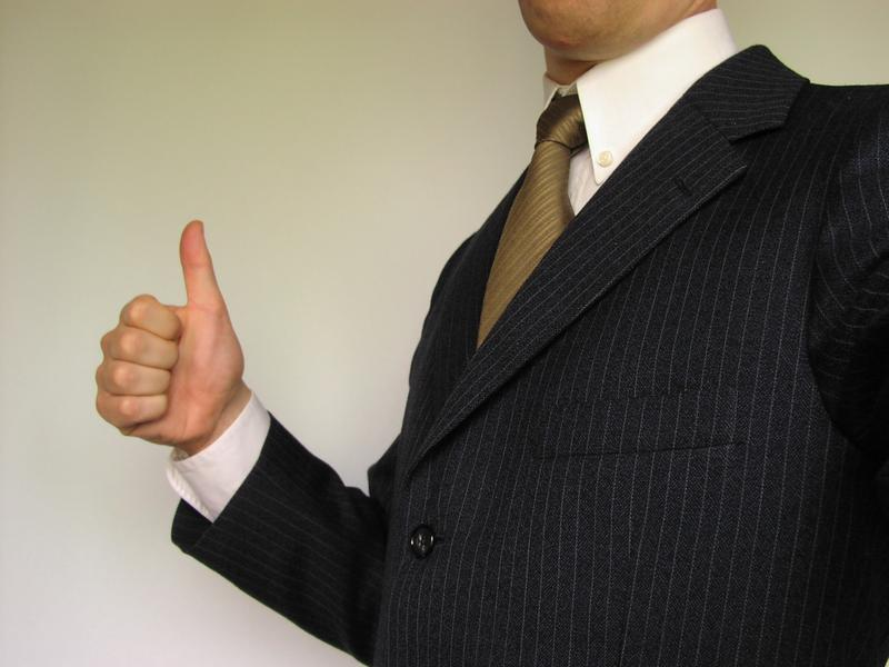 Business man in suit giving thumbs up : Free Stock Photo