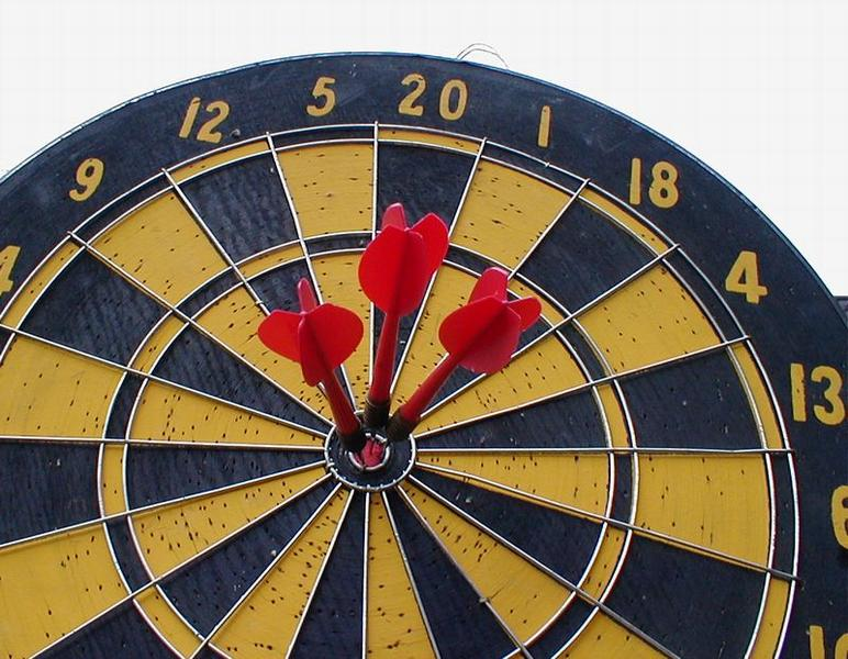 Dartboard with three darts in bullseye : Free Stock Photo