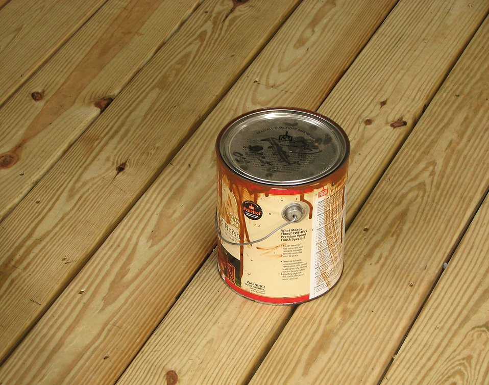 Can of wood stain on wooden deck : Free Stock Photo