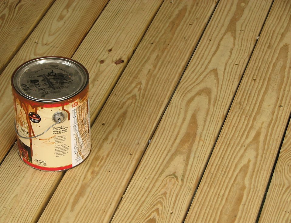 Can of wood stain on a wooden deck : Free Stock Photo