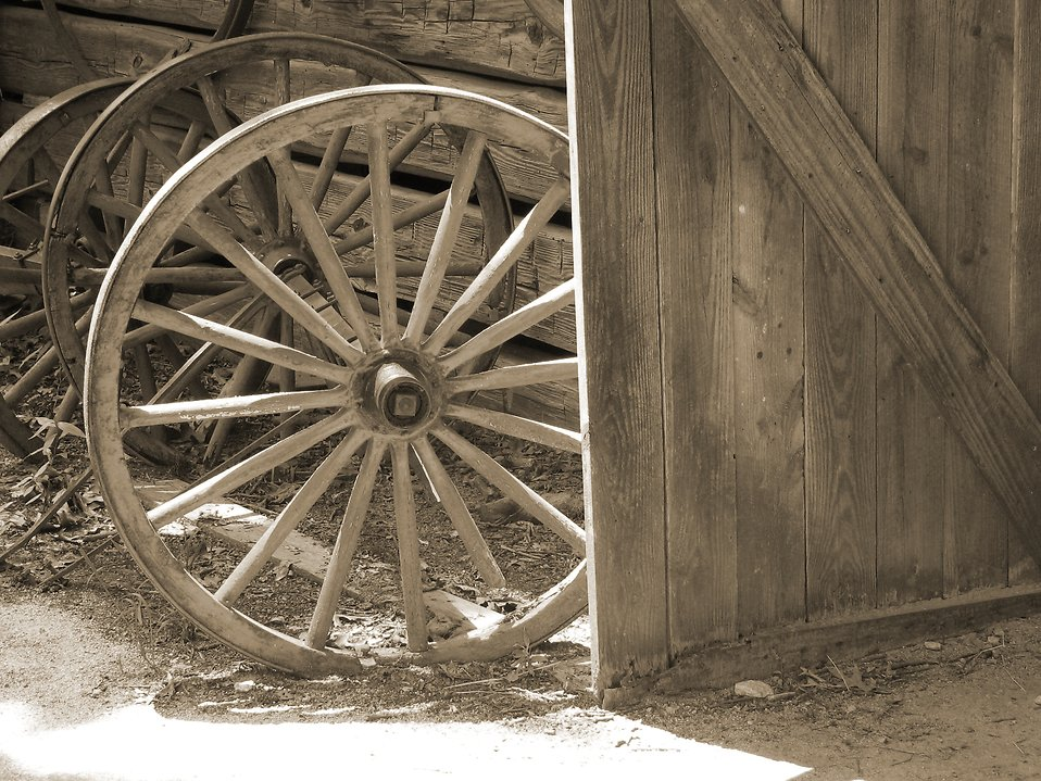 Black and white wooden wheels by a rustic barn : Free Stock Photo