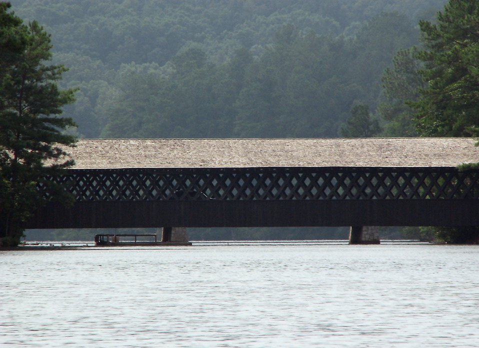 A covered bridge spanning a lake : Free Stock Photo