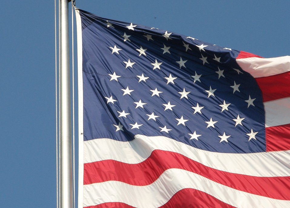 Closeup of a US flag flying on a flag pole : Free Stock Photo