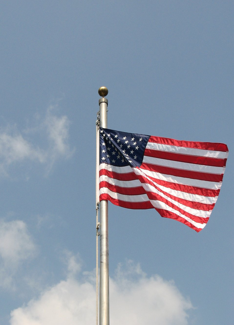 US falg on a flag pole flying a blue sky : Free Stock Photo