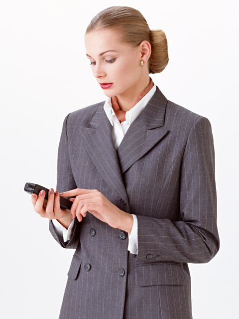 A beautiful blonde businesswoman in a suit checking a cell phone isolated on a white background : Free Stock Photo