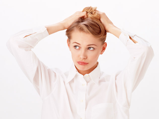 A beautiful blonde fixing her hair isolated on a white background : Free Stock Photo