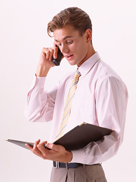 A young business man in a tie talking on a cell phone  isolated on a white background : Free Stock Photo