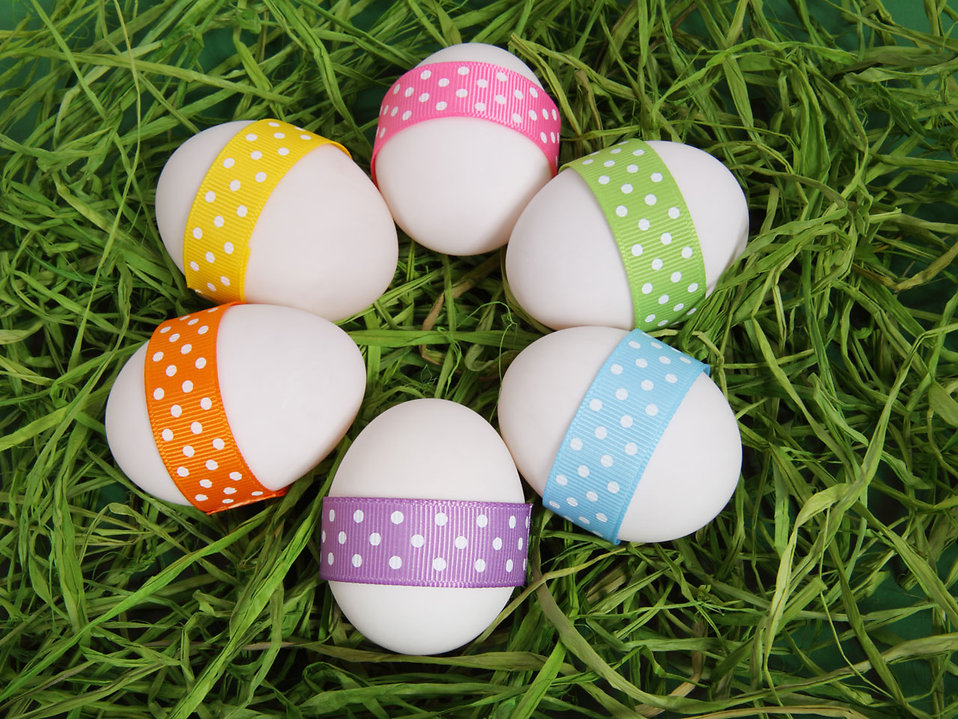Easter eggs with ribbons on grass.