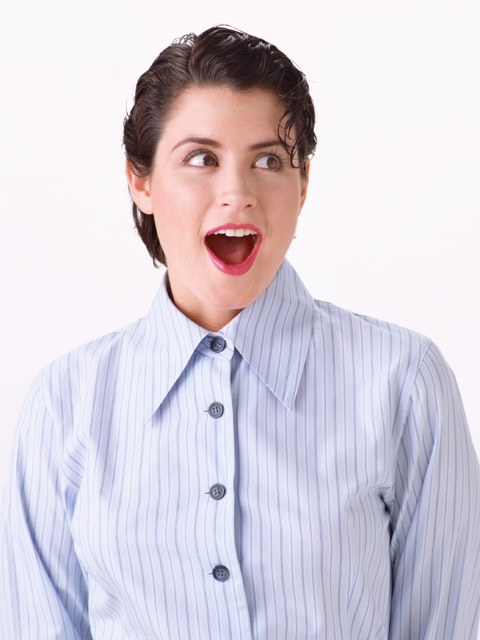 A beautiful woman acting surprised in a button down shirt isolated on a white background : Free Stock Photo