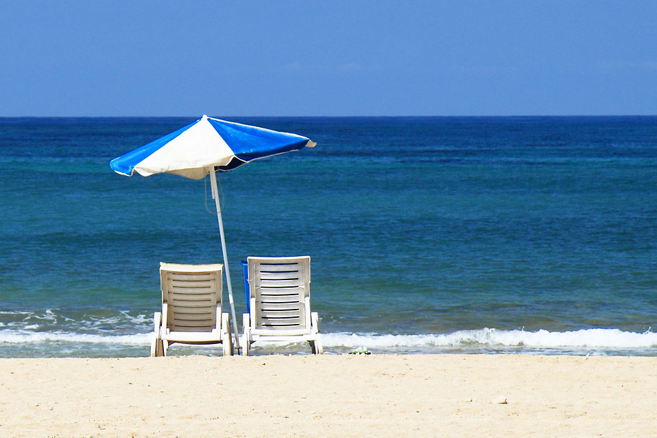 Empty beach chairs and umbrella overlooking the ocean : Free Stock Photo
