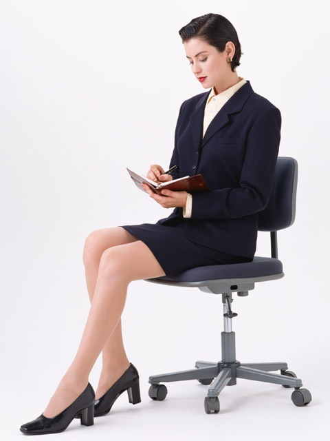 A beautiful woman in a business suit sitting in a chair isolated on a white background.