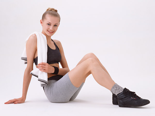 A beautiful blonde exercising isolated on a white background : Free Stock Photo
