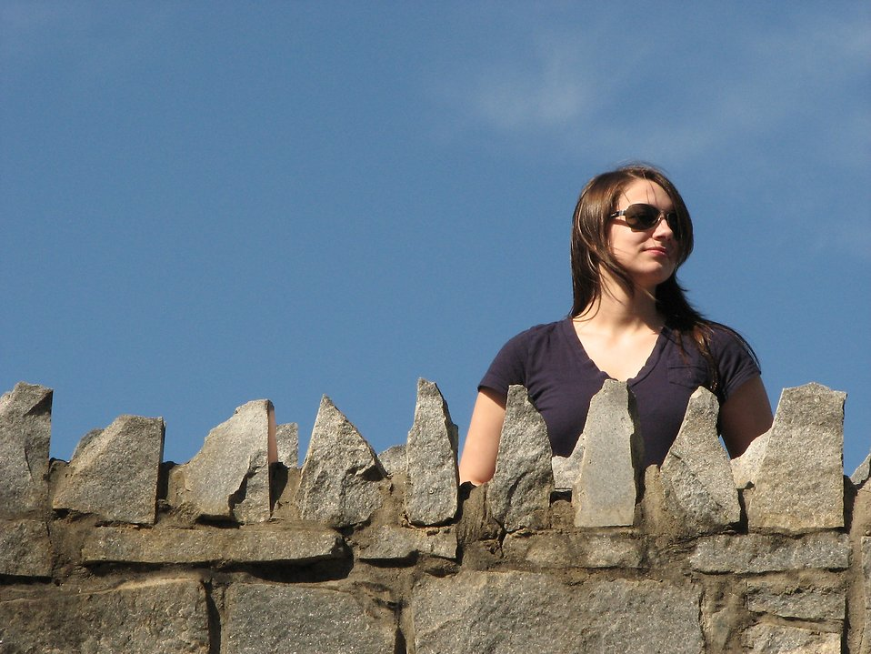 A beautiful girl standing behind a stone wall : Free Stock Photo