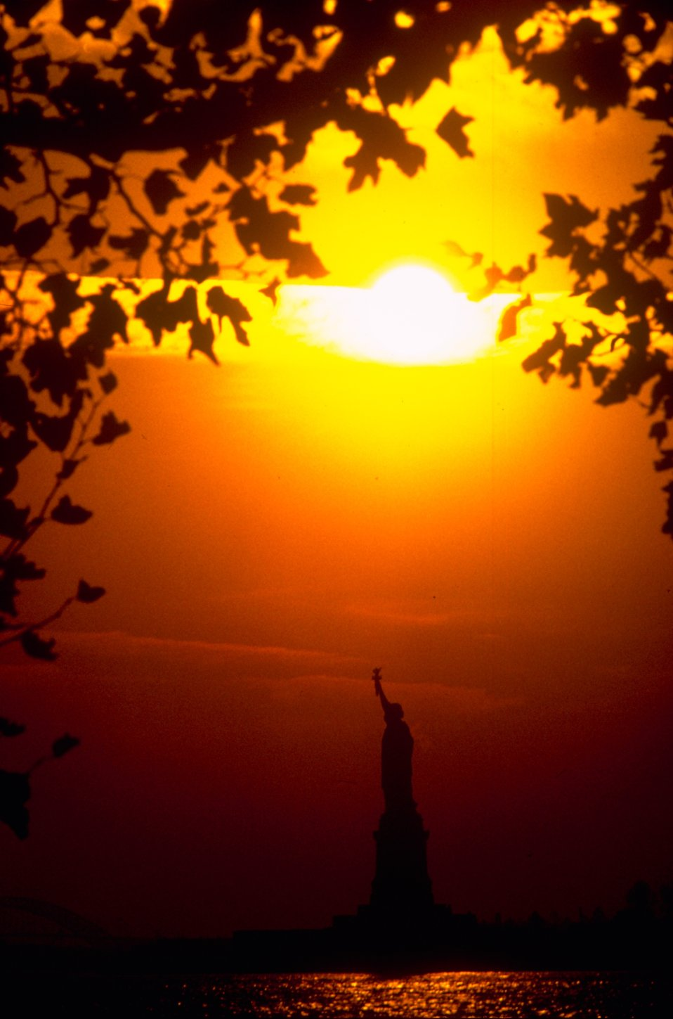 Silhouette of the Statue of Liberty monument on Liberty Island at sunset : Free Stock Photo