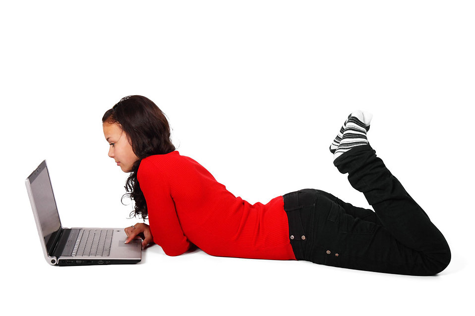 A beautiful girl lying on the floor with a laptop isolated on a white background.