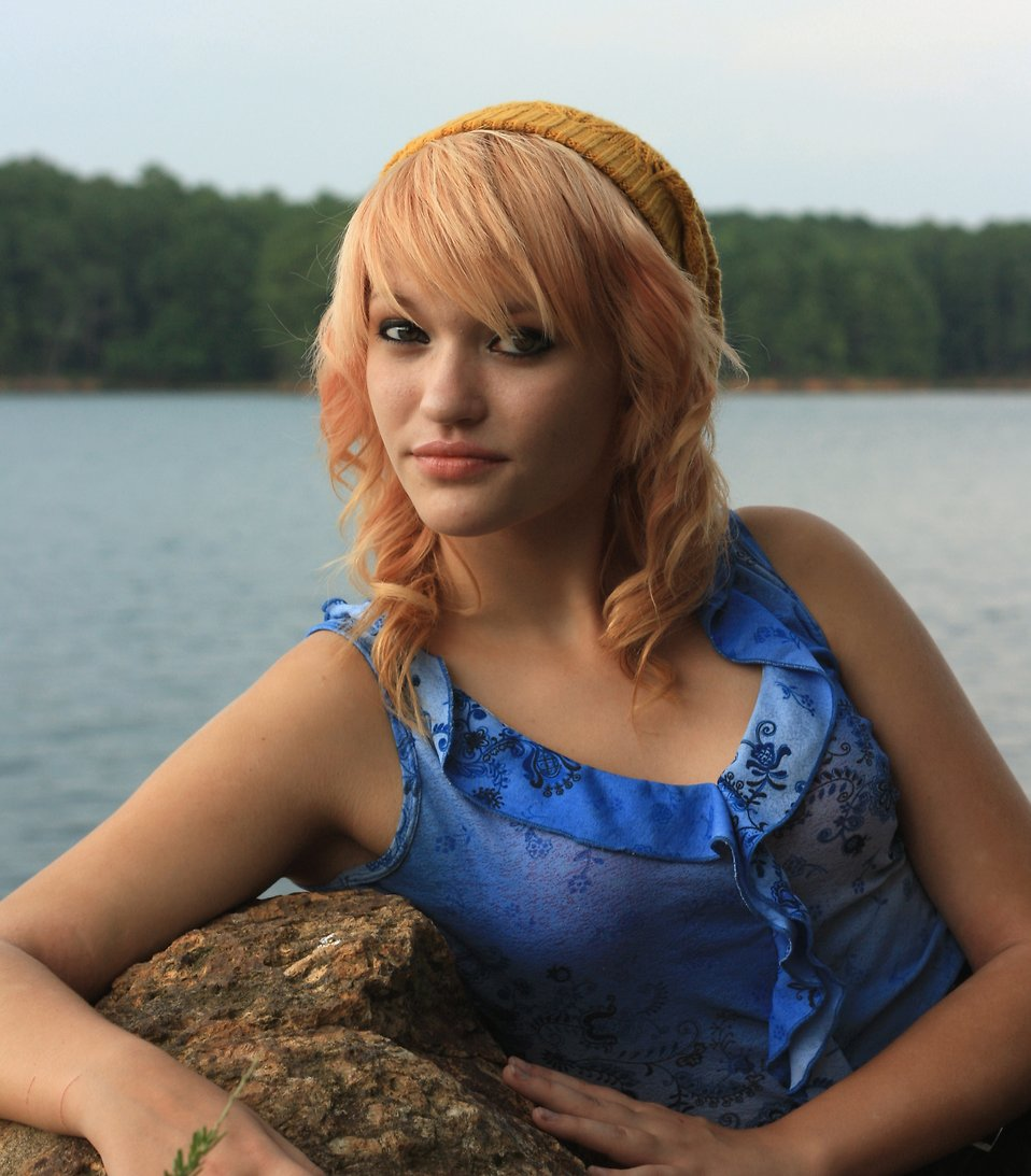 A beautiful young woman posing on a rock by a lake.