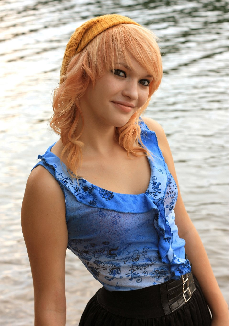 A beautiful young woman posing by a lake.