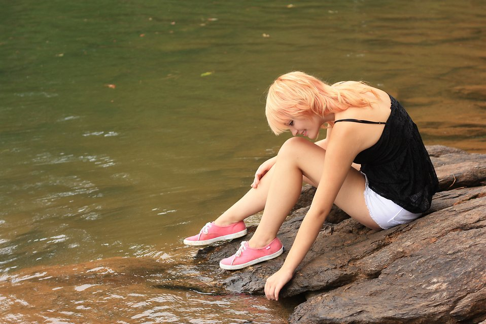 A beautiful young woman posing on a rock by a lake : Free Stock Photo