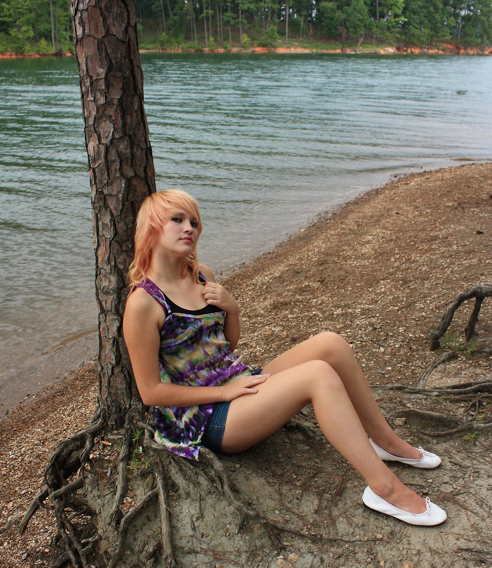 A beautiful young woman posing against a tree by a lake : Free Stock Photo