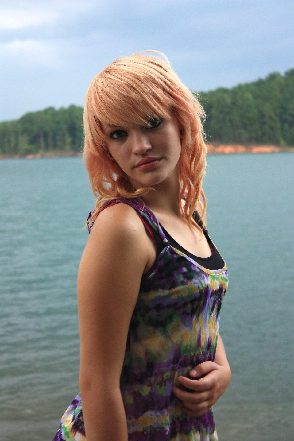 A beautiful young woman posing by a lake : Free Stock Photo