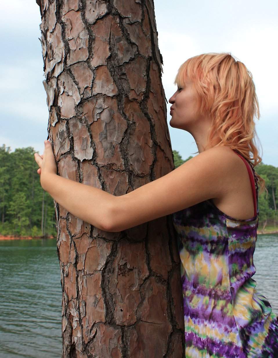 A beautiful young woman hugging and kissing a tree by a lake : Free Stock Photo