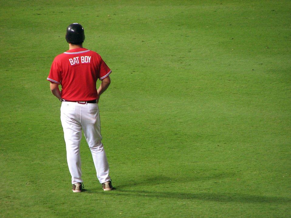 A baseball bat boy standing on a field : Free Stock Photo